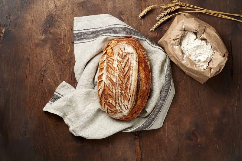 Свежо испеченные хлебцы хлеба sourdough ремесленника с шипом пшеницы и сумкой муки на темной деревянной предпосылке стоковая фотография rf