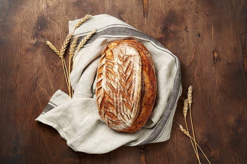 Свежо испеченные хлебцы хлеба sourdough ремесленника с шипом пшеницы и полотенцем кухни на темной деревянной предпосылке стоковые изображения rf