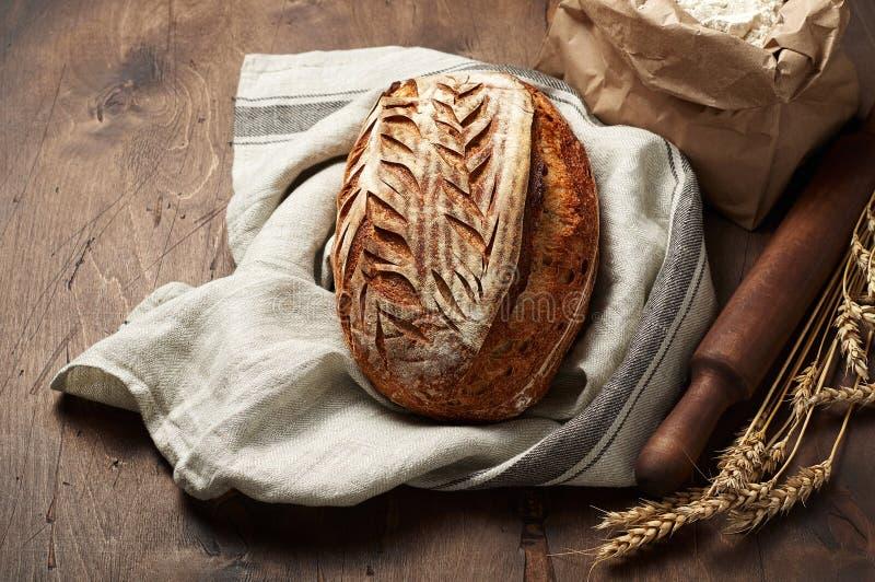 Свежо испеченные хлебцы хлеба sourdough ремесленника с шипом пшеницы и сумкой муки на темной деревянной предпосылке стоковые фото