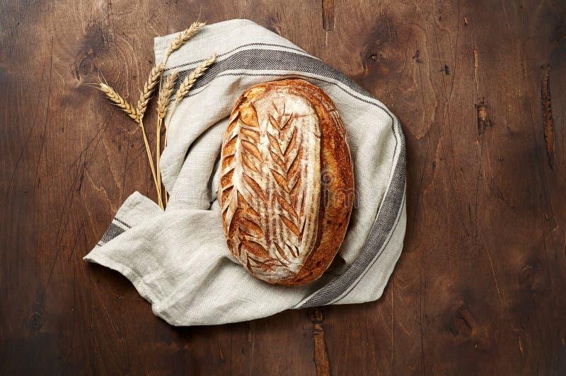 Свежо испеченные хлебцы хлеба sourdough ремесленника с шипом пшеницы и полотенцем кухни на темной деревянной предпосылке стоковое изображение rf