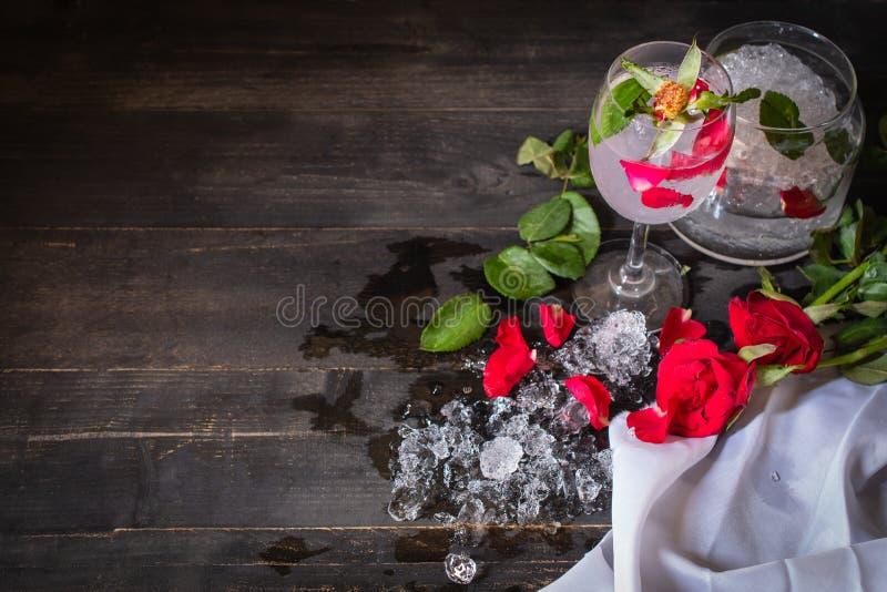 Сверкная вытрезвитель холодной воды с розой и лед на деревянной таблице там стекло розовых, diferance и лед помещенные вокруг стоковая фотография