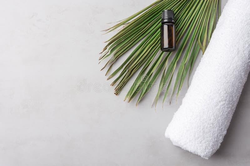 Свернутое белое чистое эфирное масло полотенца Terry хлопка в темных лист ладони бутылки на серой каменной предпосылке Сторона ко стоковая фотография