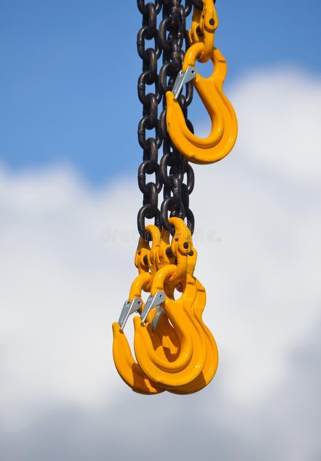 Сверхмощная цепь и желтые крюки против облака и неба стоковое фото