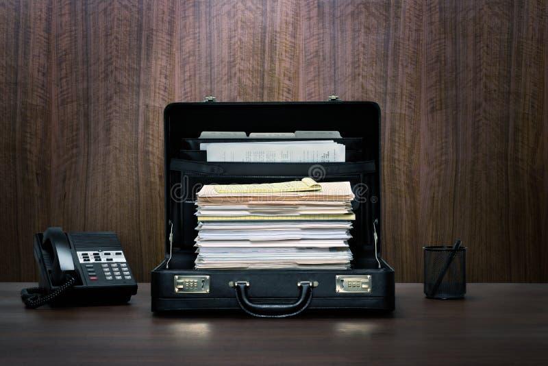 Сверхурочные! Полный набор файлов и папок в черном кожаном портфеле на столе с телефоном стоковое фото