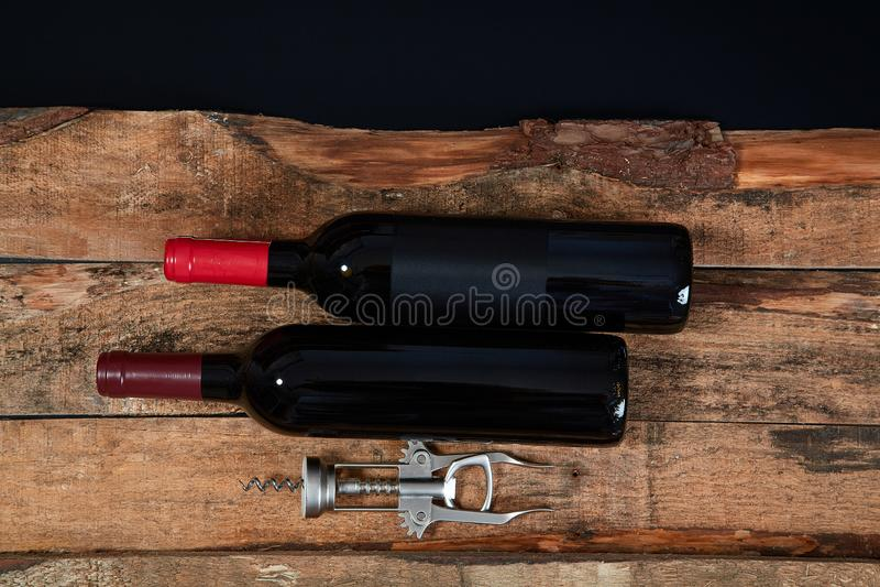 Сверху аранжированного штопора и немногий бутылка красного вина на древесине над черной предпосылкой стоковые изображения rf