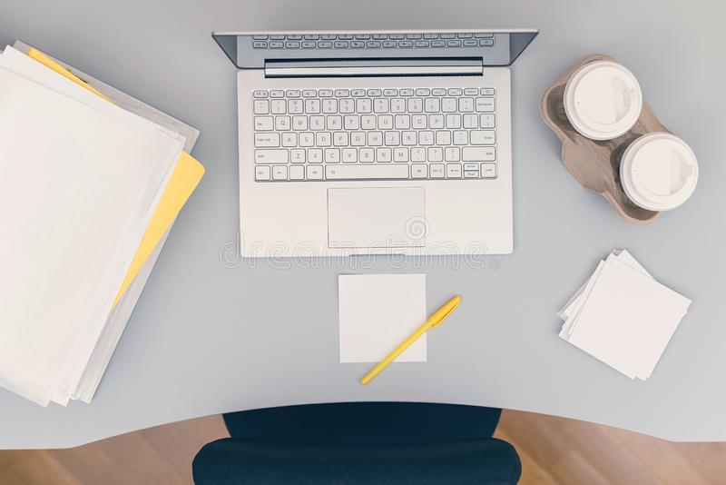 Сверху вниз части комнаты офиса включая таблицу, стул, ноутбук, бумажные стаканчики кофе, стикеры примечания и папки стоковые фото