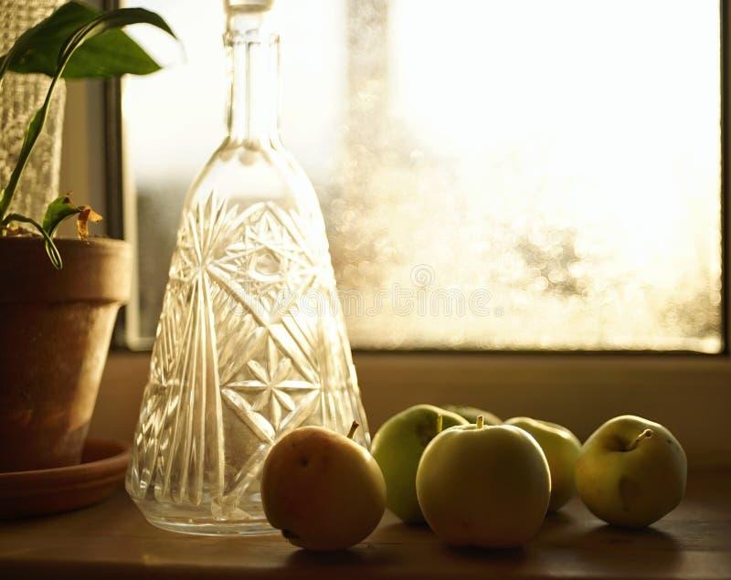 света завода конца-вверх яблок солнечного света окна бутылка крытого стеклянная стоковое изображение