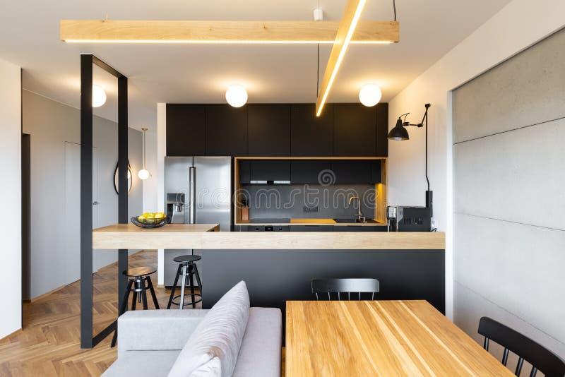 Света над countertop черной кухни в интерьере открытого пространства стоковые изображения