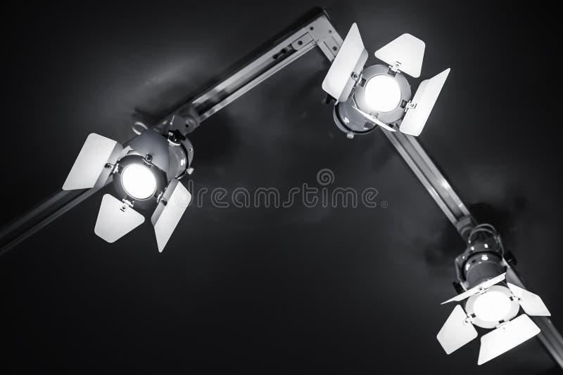 3 света пятна в теле металла над чернотой стоковые изображения