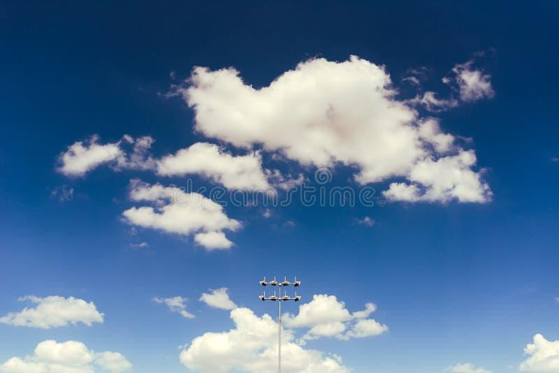 Света стадиона против голубого неба с белым clodus стоковые фотографии rf