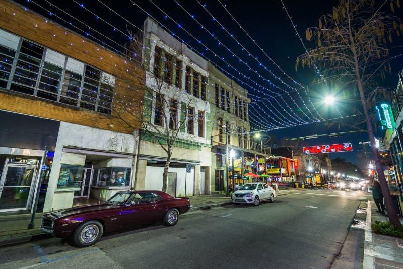 Света строки повиснули над улицей дофина, и зданиями в городской черни, Алабаме стоковое изображение