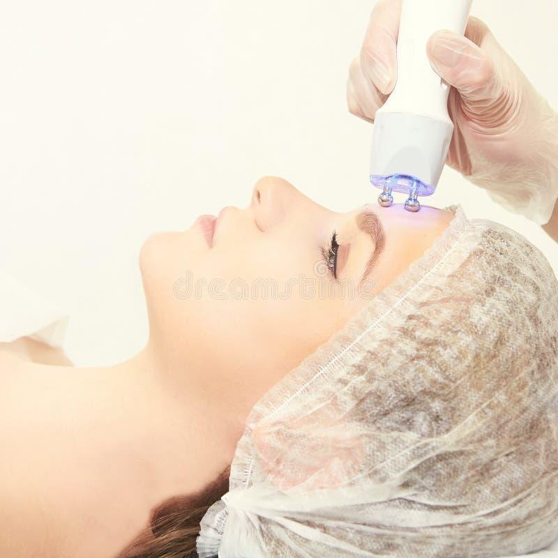 Светлая ультракрасная терапия Процедура по головы косметологии Сторона женщины красоты Косметический прибор салона Лицевое подмол стоковое фото rf