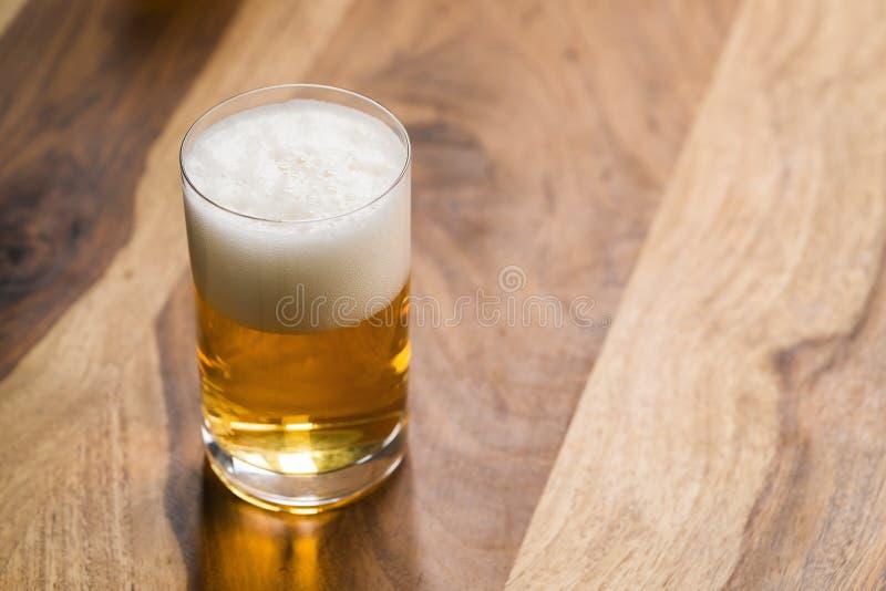 Светлое пиво в стекле на деревянной предпосылке с космосом экземпляра стоковые изображения rf