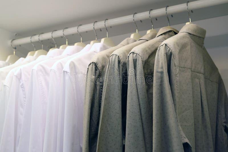 Светлые и темные рубашки в шкафе на вешалке стоковое фото