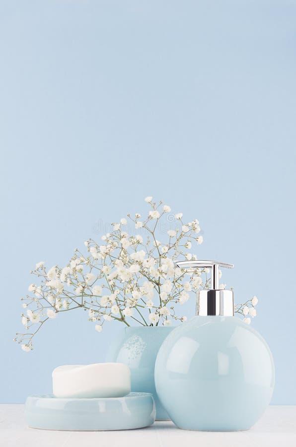 Светлые пастельные голубые аксессуары для ванны и кожи и тела заботят продукт - мыло, распределитель мыла, полотенце на белой дер стоковая фотография rf