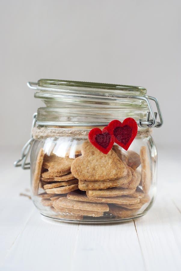 Светлые печенья в опарнике украшенном с 2 красными сердцами стоковые изображения