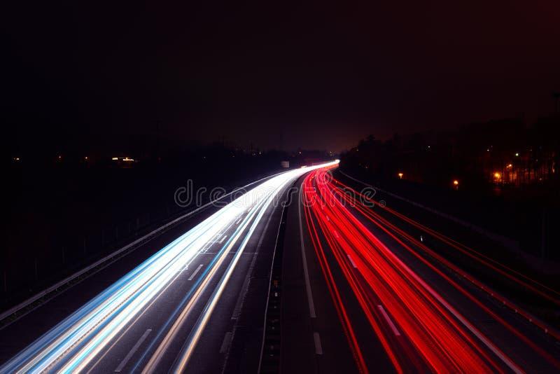 Светлые следы автомобилей вечером на шоссе стоковое фото
