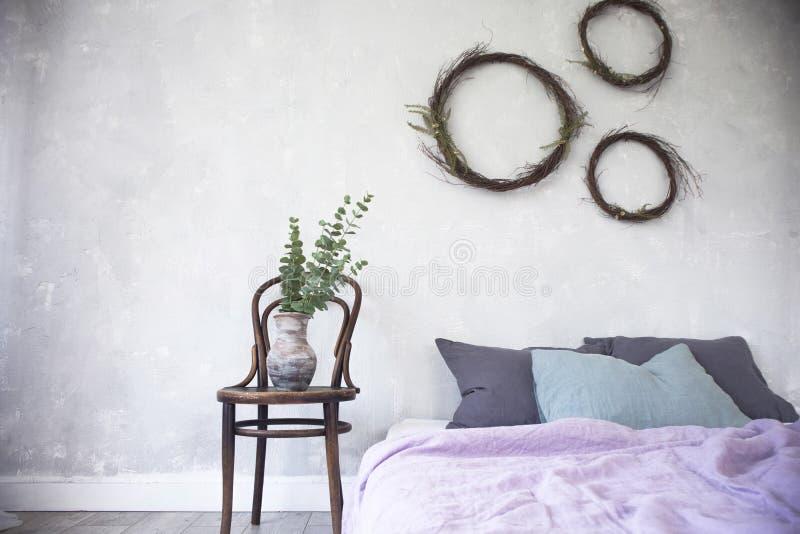 Светлый интерьер, дизайн сделанный в серых и фиолетовых цветах с современной мебелью, конец вверх кровати и ваза спальни стиля пр стоковое изображение rf