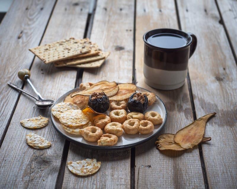 Светлый обед с печеньями чая и зерна, высушенными плодами на деревянной деревенской таблице стоковая фотография