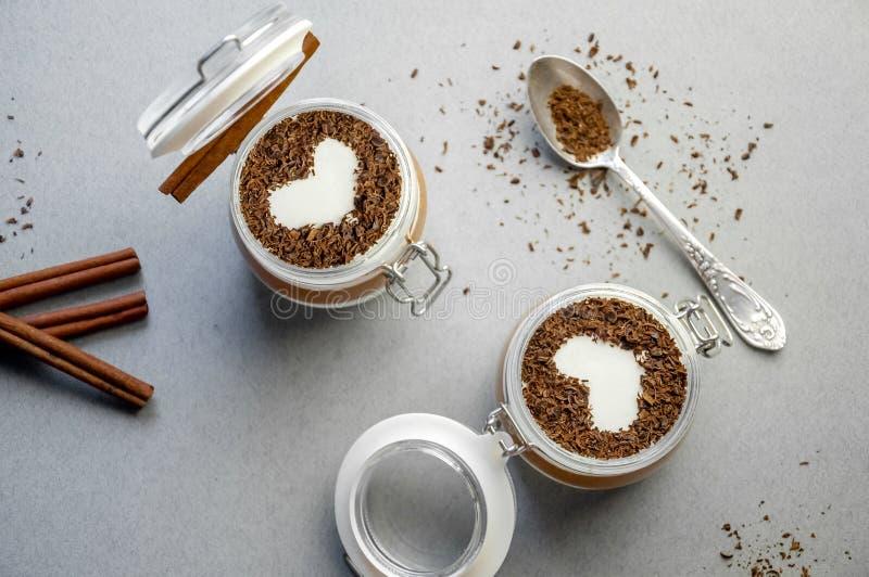 Светлый сметанообразный десерт мусса ванили и шоколада в стекле на серой предпосылке день ` s валентинки концепции Плоское положе стоковые фотографии rf