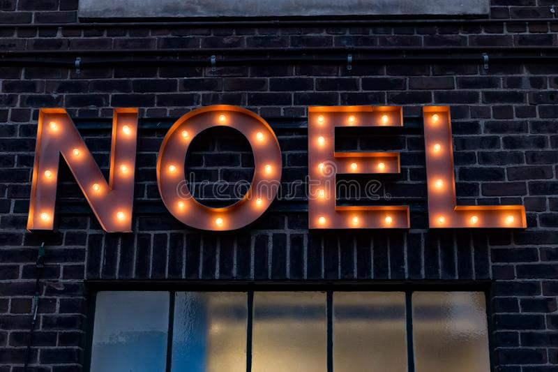 Световой сигнал NOEL на кирпичной стене стоковые фотографии rf