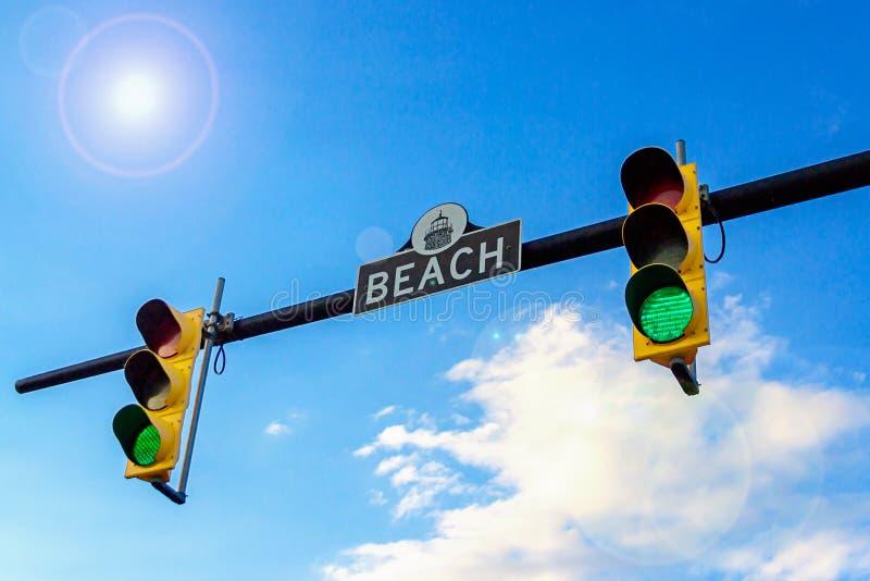 2 светофоры и ПЛЯЖА знака улицы Светофор с зеленым светом Голубое небо со слепимостью солнца стоковые фото