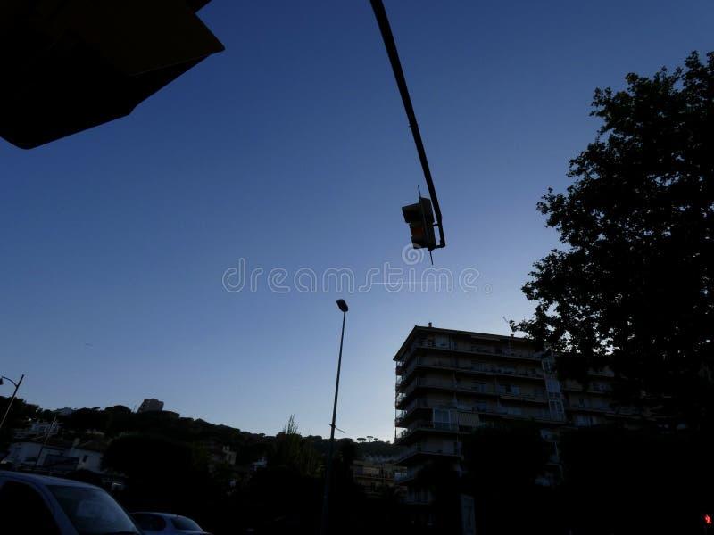 Светофор внутри освещает контржурным светом на предпосылке голубого неба стоковое изображение rf