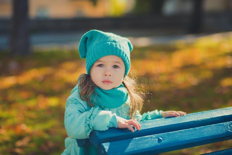 Свет бирюзы toothsome маленькой девочки штыря-вверх тележки нося - синий пиджак и теплая шляпа фасонируют стильные одежды предста стоковая фотография rf