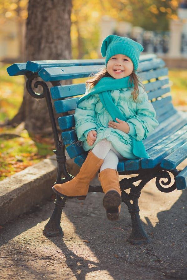 Свет бирюзы toothsome маленькой девочки штыря-вверх тележки нося - синий пиджак и теплая шляпа фасонируют стильные одежды предста стоковые фото