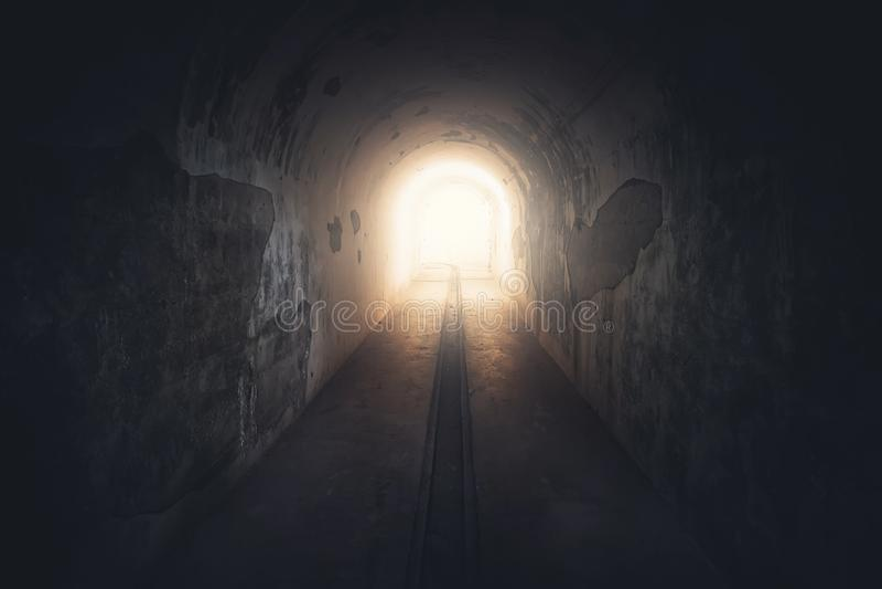 Свет в конце тоннеля Длинный подземный конкретный коридор в получившемся отказ тонизированном бункере, стоковые фото