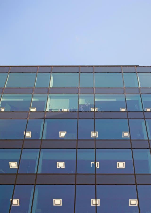 Свет в окнах современного здания стеклянного офиса освещается в сумерках стоковая фотография