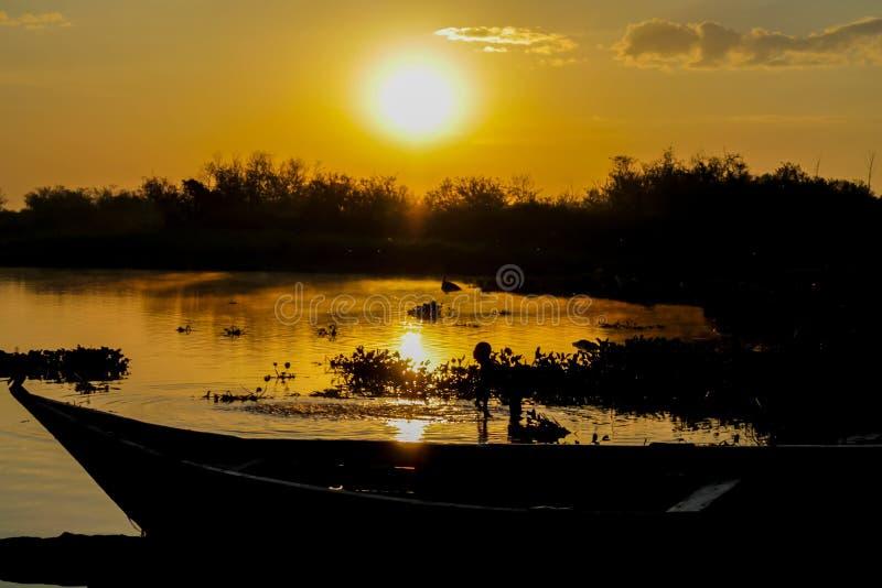 Свет захода солнца на озере с шлюпкой и девушкой в воде стоковые фото