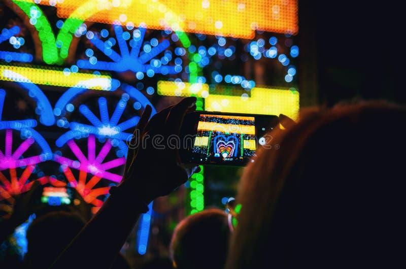 Свет и представление музыки записанное со смартфоном, который держит рука женщины во время Cuneo Illuminata стоковые фото