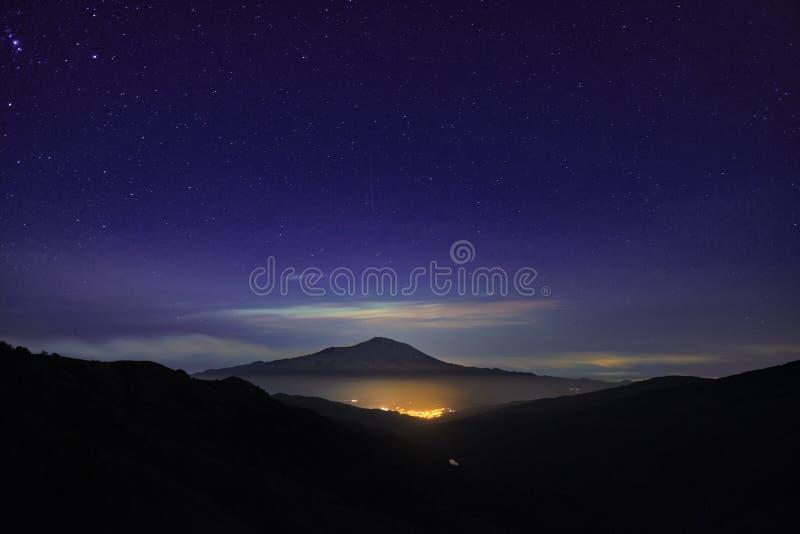 Свет ночи городка Randazzo накаляя под держателем и небом Этна вполне звезд от парка Nebrodi стоковые изображения rf
