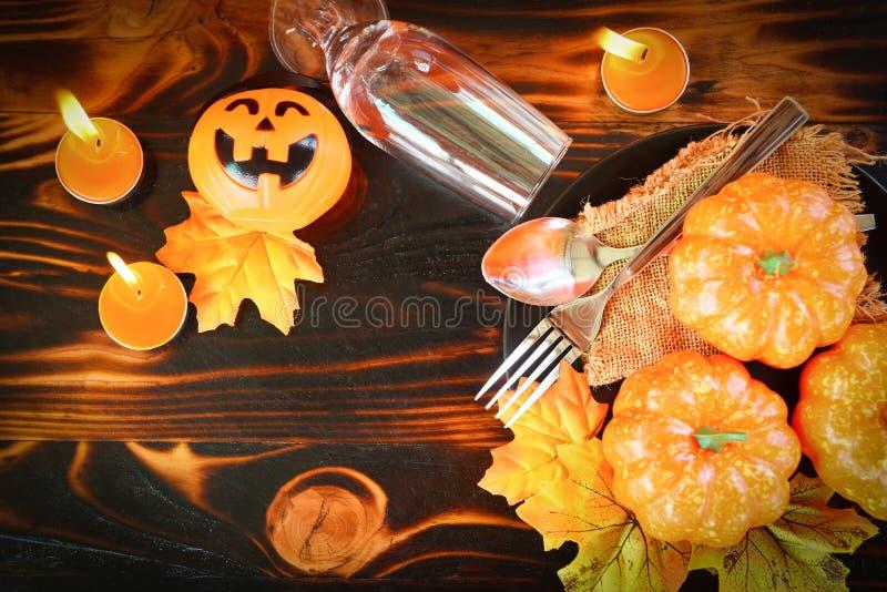 Свет свечи праздника аксессуаров украшения сервировки стола хеллоуина с вилкой ложки шампанского стеклянной и тыква поднимают фон стоковые изображения