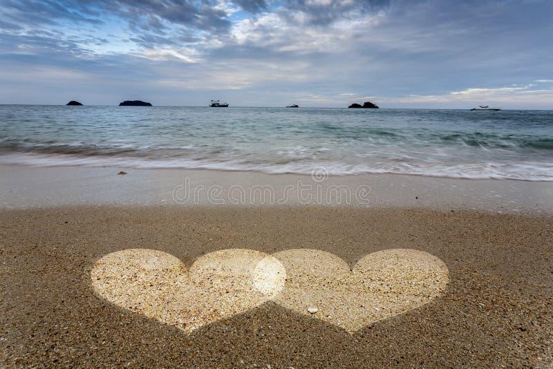 Свет сердец в песке на пляже океана стоковое фото