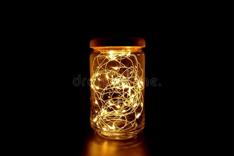 Свет феи в стеклянном опарнике на черной предпосылке стоковые изображения