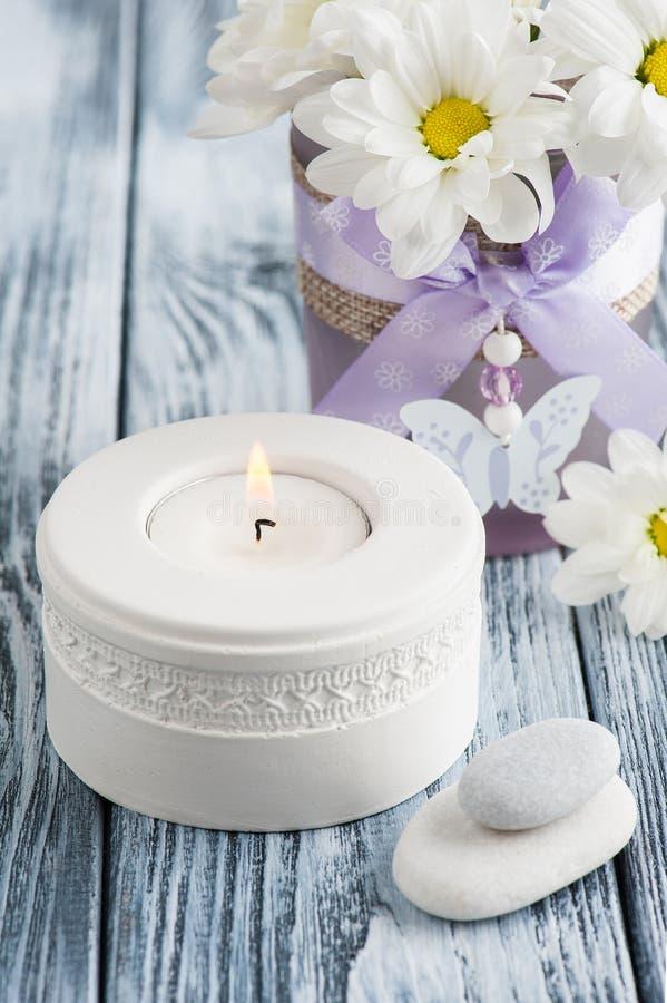Свеча и камешки над затрапезной деревянной предпосылкой стоковые фото