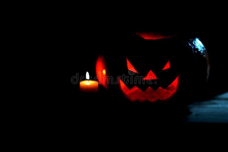 Свеча и страшная усмехаясь тыква на хеллоуин стоковое изображение