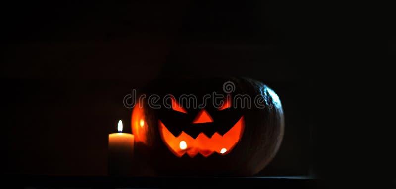 Свеча и страшная усмехаясь тыква на хеллоуин стоковые изображения