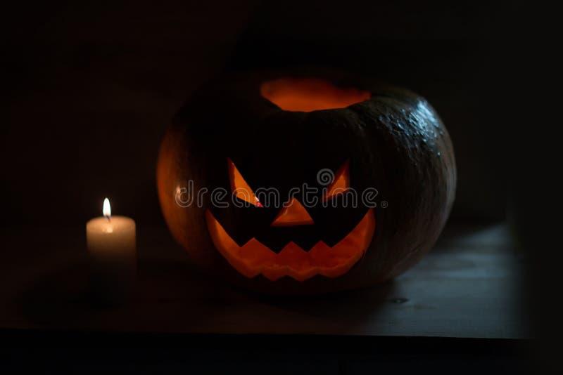 Свеча и страшная усмехаясь тыква на хеллоуин стоковая фотография rf