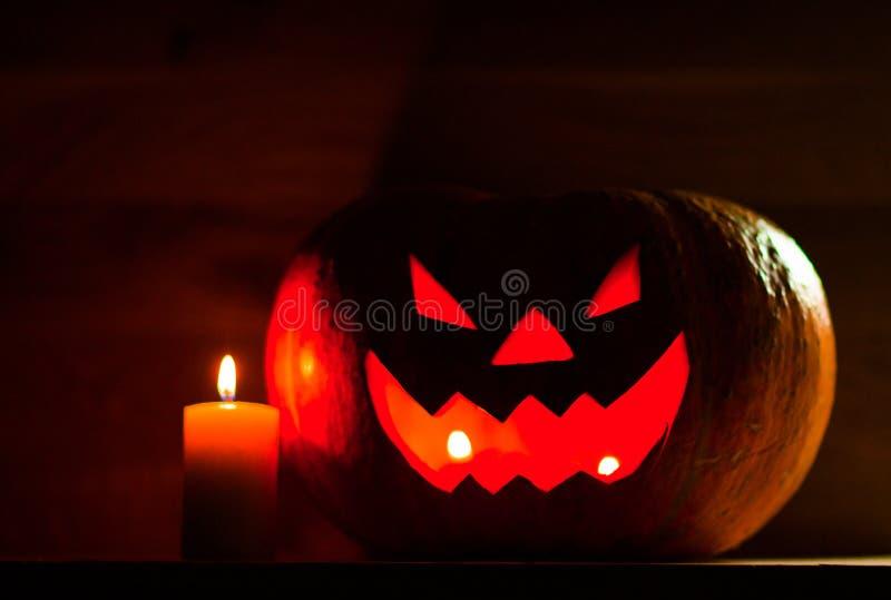 Свеча и страшная усмехаясь тыква на хеллоуин стоковое фото