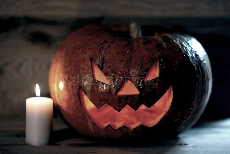 Свеча и страшная усмехаясь тыква на хеллоуин стоковое фото rf