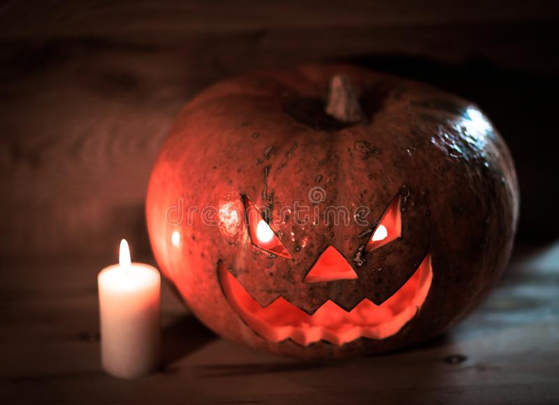 Свеча и страшная усмехаясь тыква хеллоуина на деревянном столе стоковые изображения