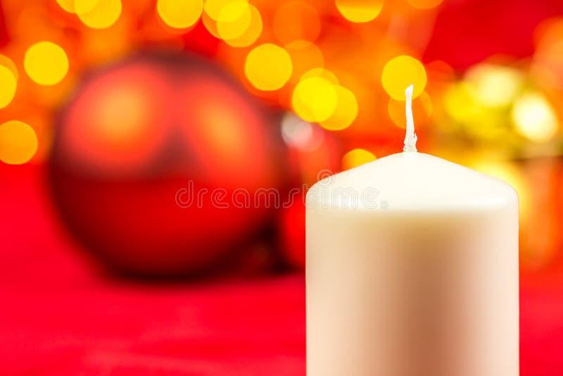 Свеча и шарики воска белого рождества на красной предпосылке стоковая фотография