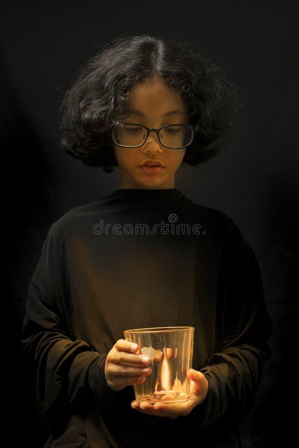 Свеча освещена в стекле, который держит красивая женщина в черноте Изолированный на концепции сохранения энергии земли стоковые изображения rf