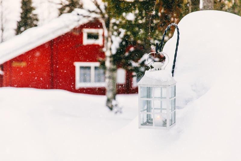 Свеча рождества в фонарике Красный деревянный коттедж в сельской снежной Финляндии стоковое изображение