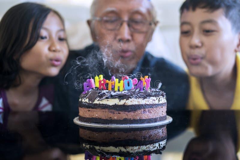 Свечи дня рождения дуновения старика и внуков стоковое фото rf