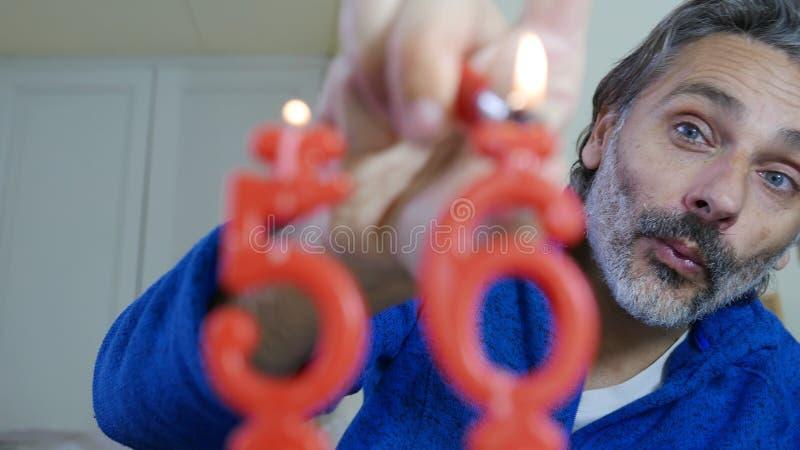 Свечи дня рождения освещения человека стоковые изображения