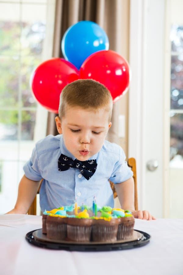 Свечи мальчика дуя на торте стоковая фотография rf